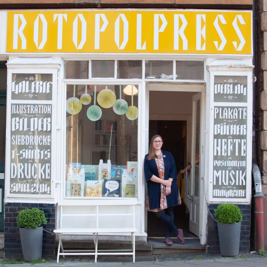 Rita Fürstenau - lehnt an Türrahmen von Geschäft